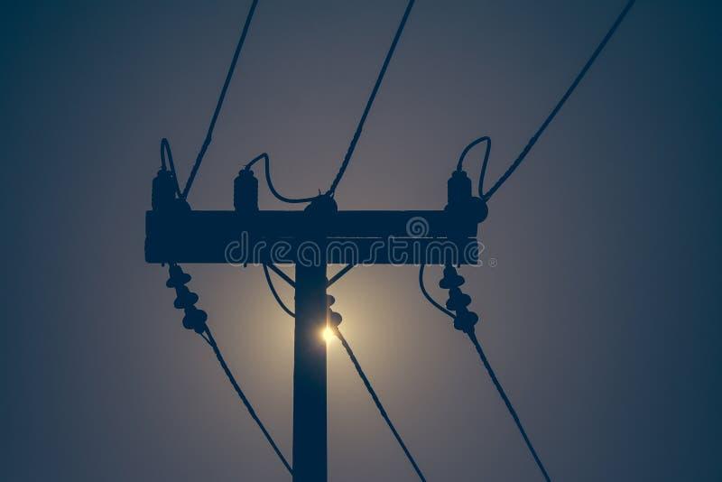 电杆和高压输电线剪影与日落在背景中 免版税库存图片