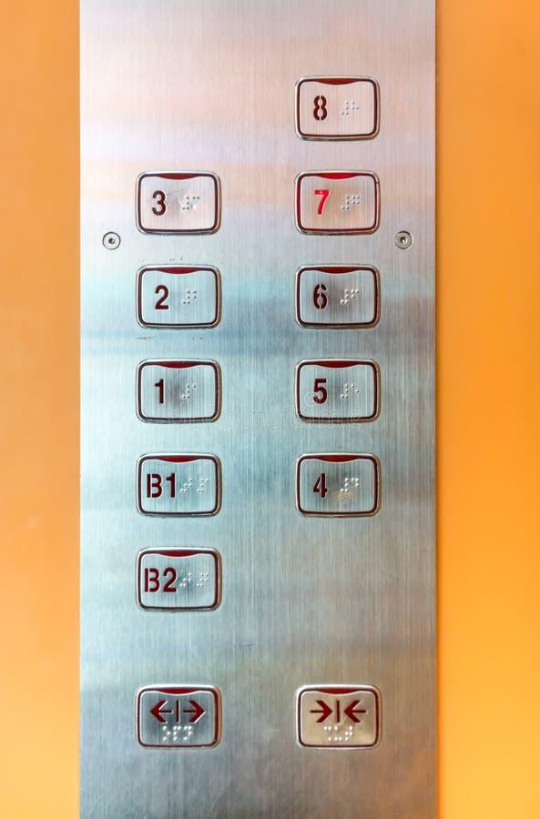 电梯按与掠过的金属纹理表面板材的盘区 库存照片
