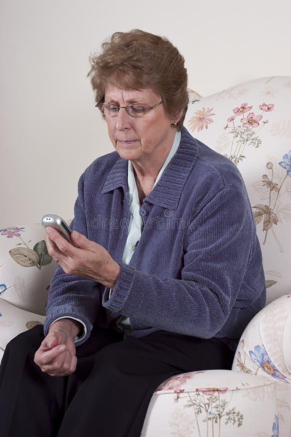 电池关心成熟电话高级texting的妇女 免版税图库摄影