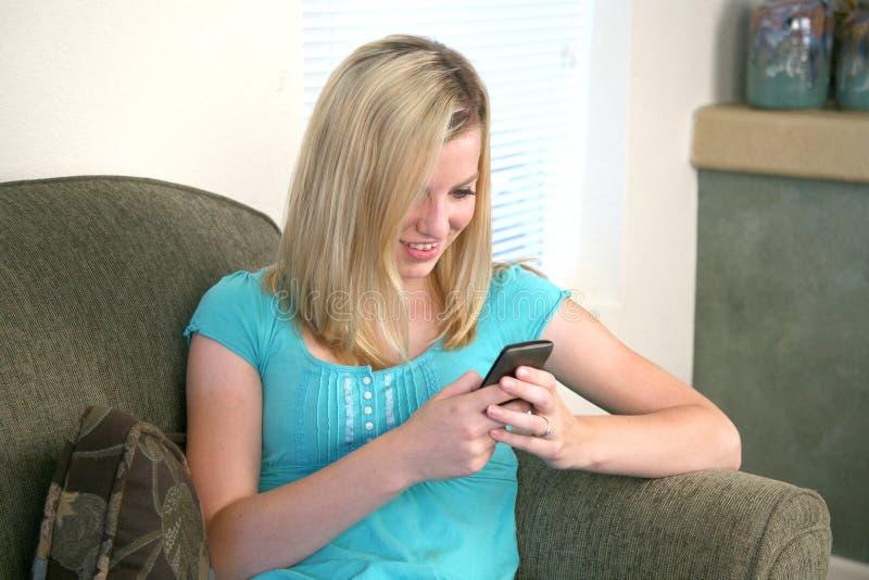 电池女孩她的电话texting的年轻人 免版税库存图片