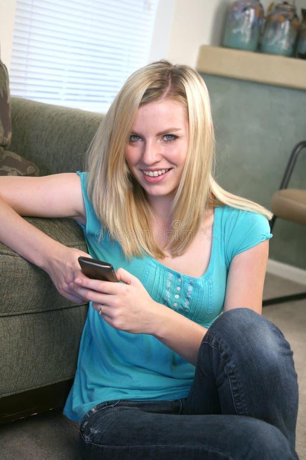电池女孩她的电话texting的年轻人 免版税库存照片