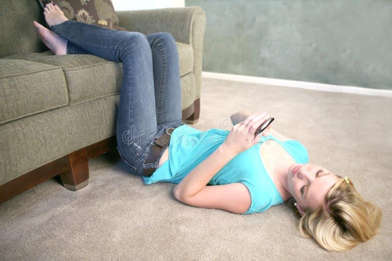 电池楼层电话texting的妇女 库存图片