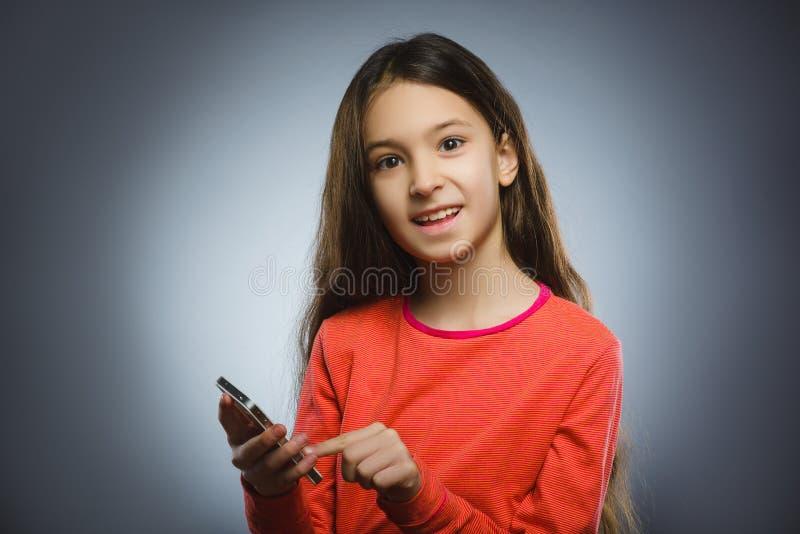 电池逗人喜爱的女孩一点电话告诉 查出在灰色 免版税库存图片