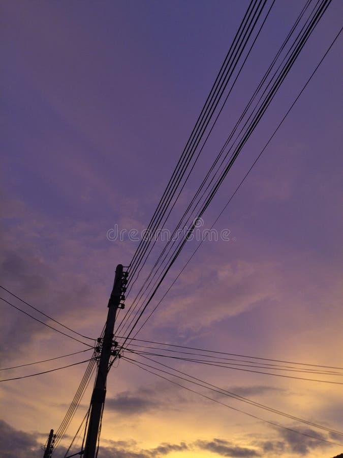 电源杆和日落美好的天窗  免版税库存照片