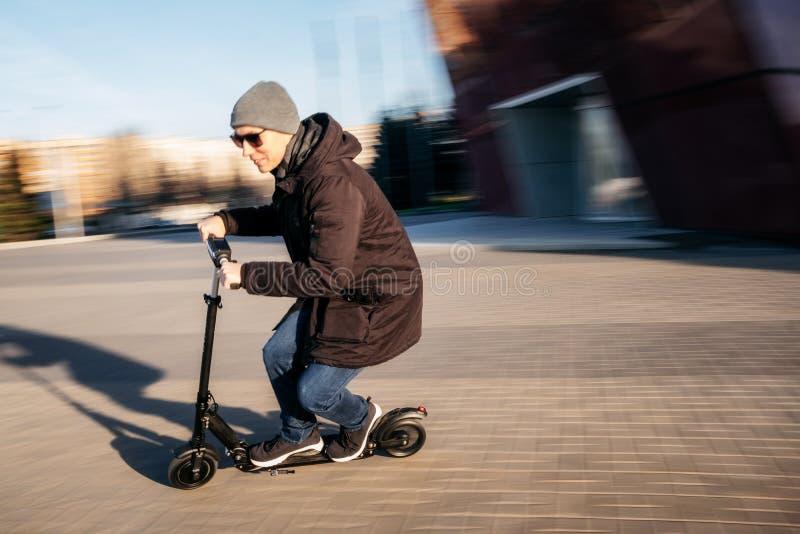 电滑行车的年轻人在街道上 图库摄影