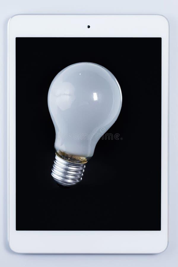 电灯泡和片剂个人计算机 库存照片