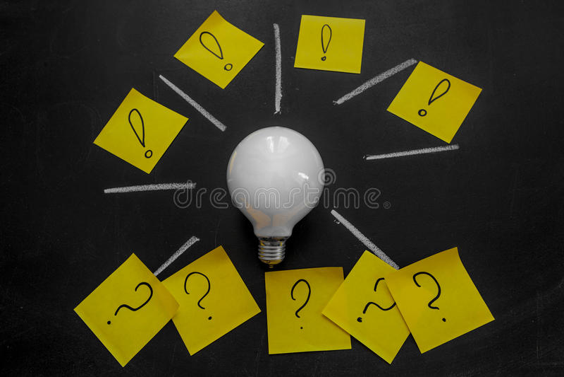 电灯泡和黄色贴纸在黑黑板 免版税图库摄影