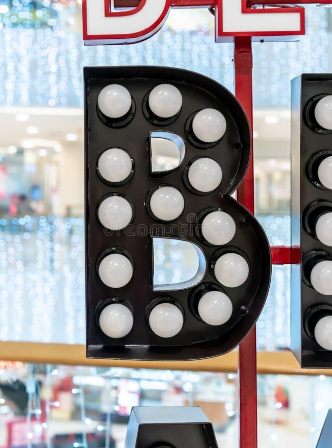 电灯泡哥特式黑体字垂悬在红色金属框架的字母表字符B 免版税库存图片