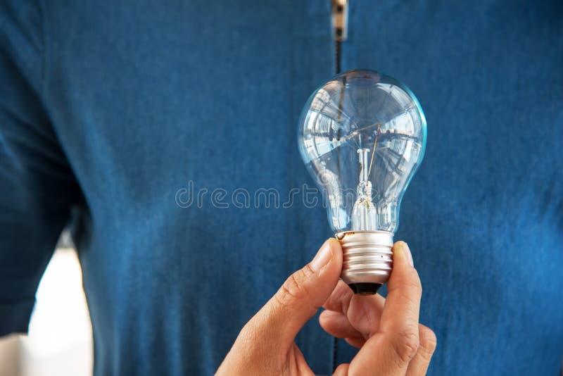 电灯泡在妇女手上 想法和创造性的概念 成功和 库存图片