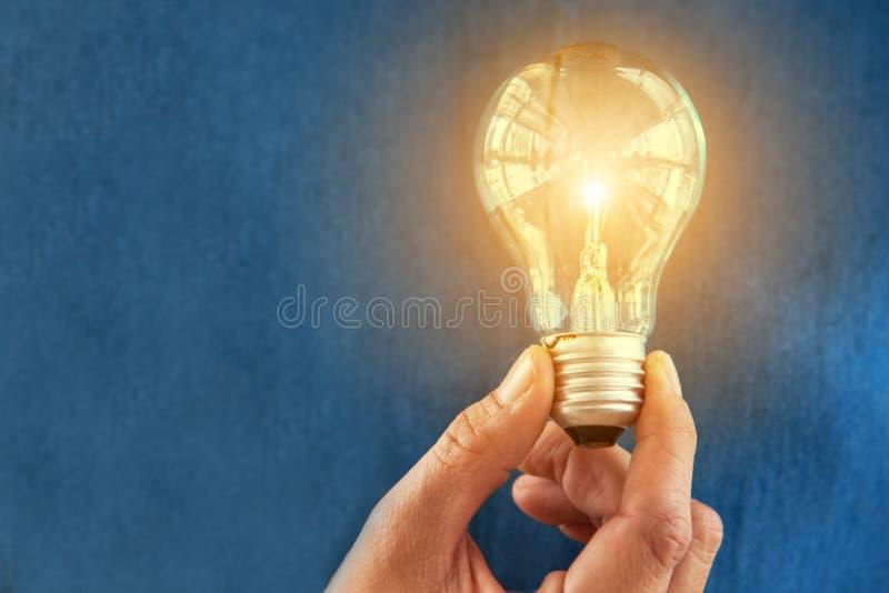 电灯泡在有橙色光的妇女手上 想法和创造性的概念 成功和想法的概念 对象和人题材 免版税库存照片
