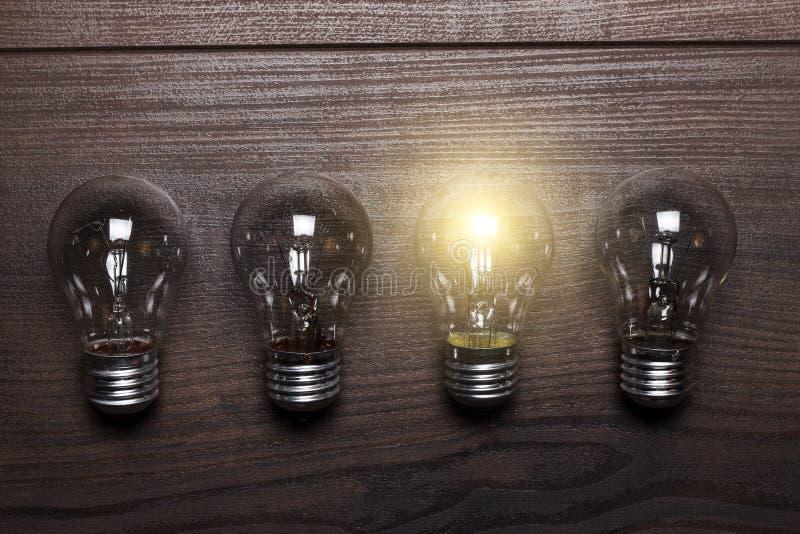 电灯泡在木背景的唯一性概念 免版税库存照片