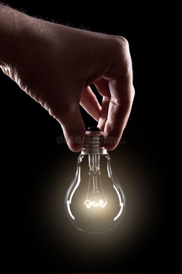 电灯泡用手 库存图片