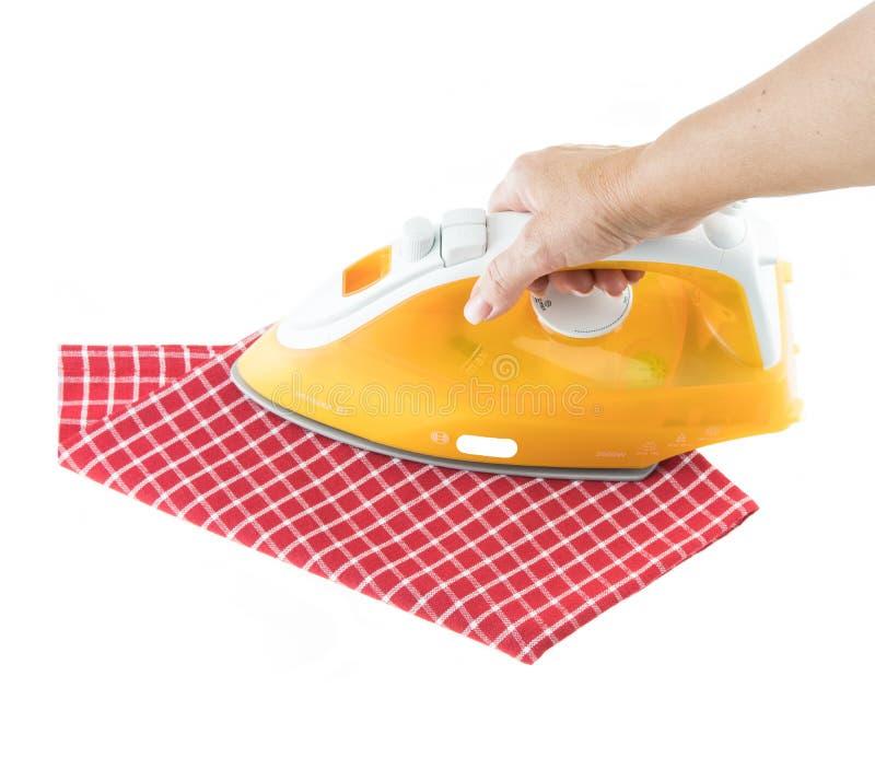 电烙与黄色铁的妇女手红色白色方格的洗碗布在白色被隔绝 免版税库存照片