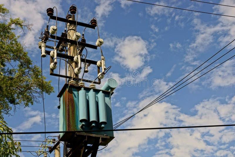 电烙在一根杆的生锈的电子变压器与导线 免版税库存照片
