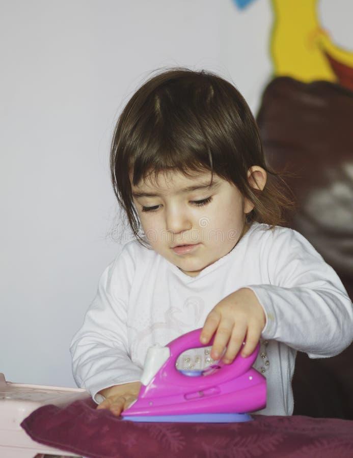 电烙有铁玩具的小逗人喜爱的孩子衣裳 图库摄影