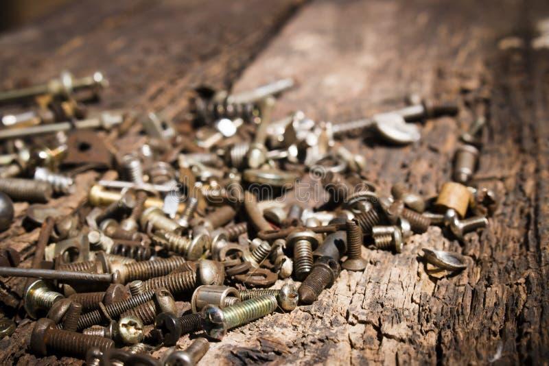 电烙生锈的工具螺栓和螺丝在一个老木桌特写镜头 库存照片