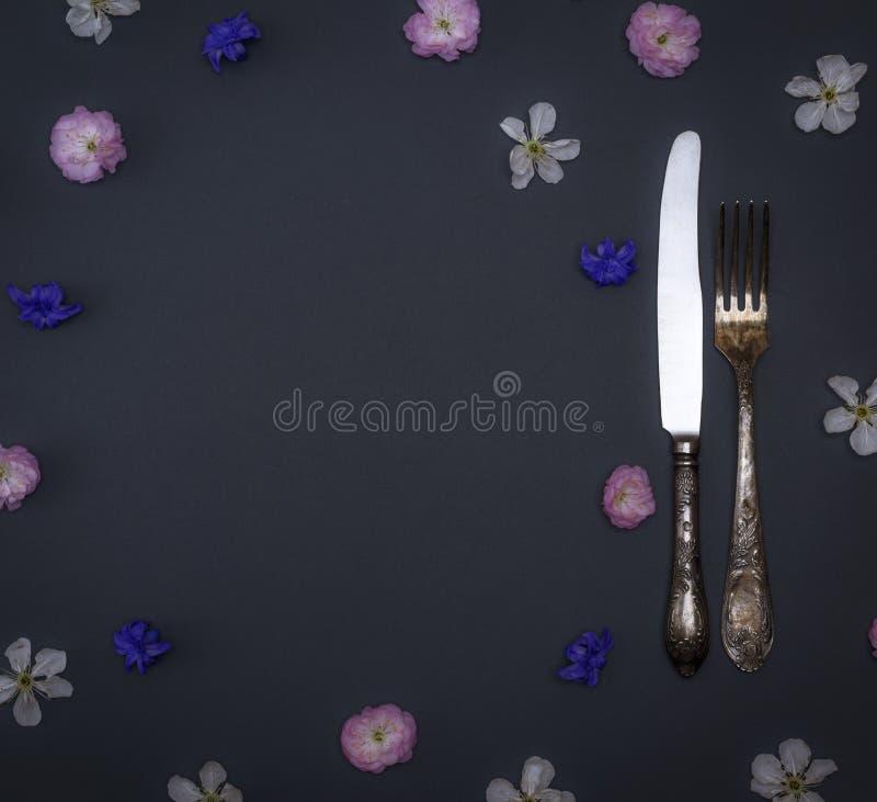 电烙葡萄酒利器叉子和刀子在黑背景 免版税库存图片