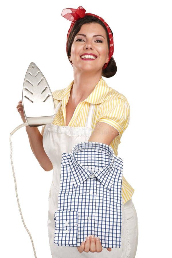 电烙衬衣的愉快的美丽的妇女主妇 免版税库存照片