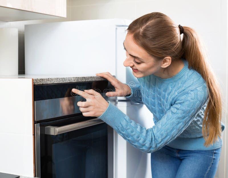 给电烤箱加热的微笑的美丽的年轻主妇 免版税库存照片