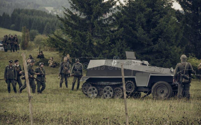 电烫,俄罗斯- 2016年7月30日:二战,夏天的历史再制定1942年 德国士兵和防弹车 库存照片