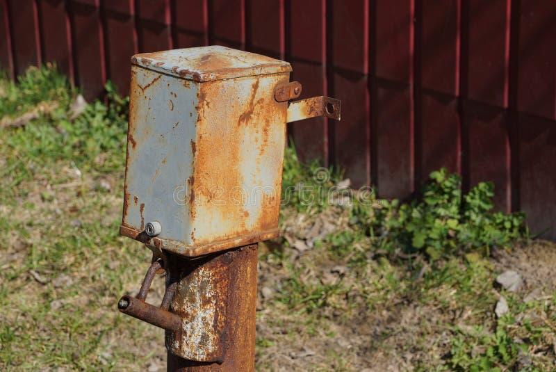 电的老灰色棕色生锈的金属箱子在篱芭之外的一根杆 免版税库存图片