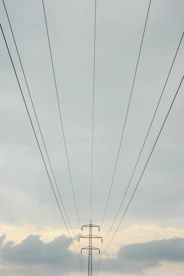 电线关闭定向塔 高压塔和多云天空 免版税库存图片