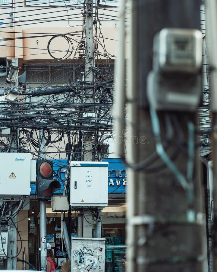 电线和电话电缆用一个杂乱方式在大厦在曼谷 免版税库存照片