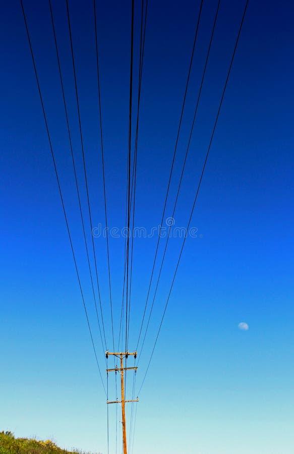 电线杆和电导线和缆绳,天空蔚蓝,月亮 库存图片