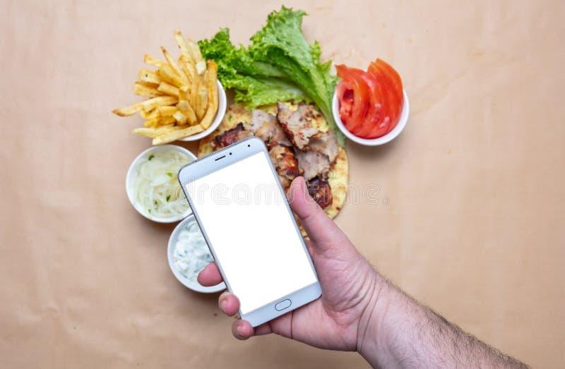 电罗经和智能手机 拿着有空白的白色屏幕的,电罗经皮塔饼成份背景的手一个手机 库存照片