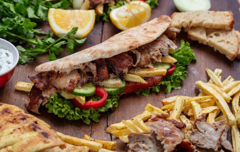 电罗经,shawarma,拿走,街道食物 三明治用在木桌上的肉 图库摄影
