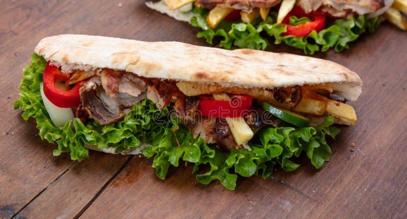 电罗经,shawarma,拿走,街道食物 三明治用在木桌上的肉 库存图片
