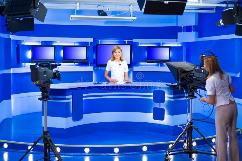 电视女主持人和遥控机器人在电视演播室工作 免版税库存照片