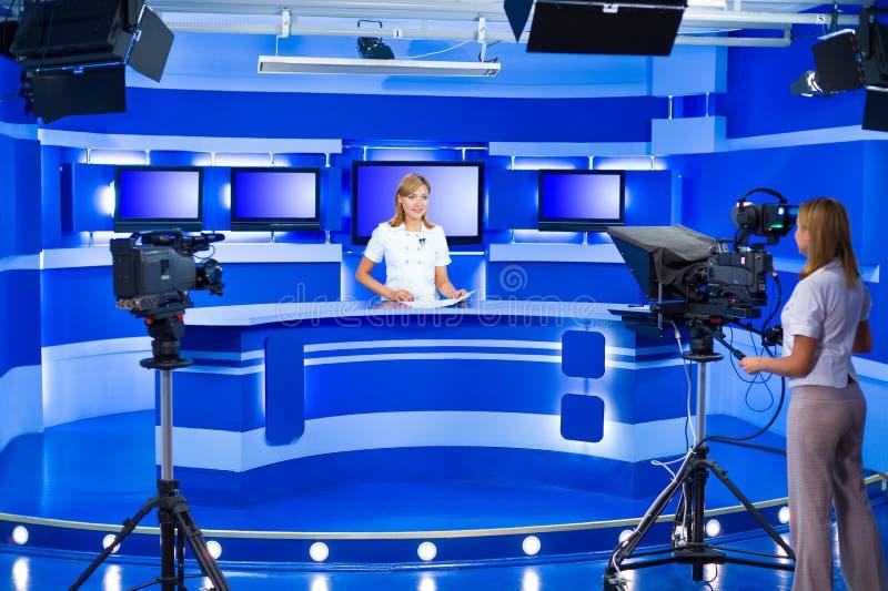 电视新闻广播员和遥控机器人在电视演播室 免版税库存图片