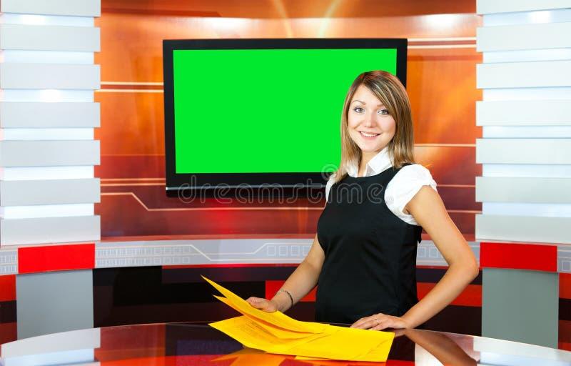 电视演播室的怀孕的电视女主持人 免版税库存图片