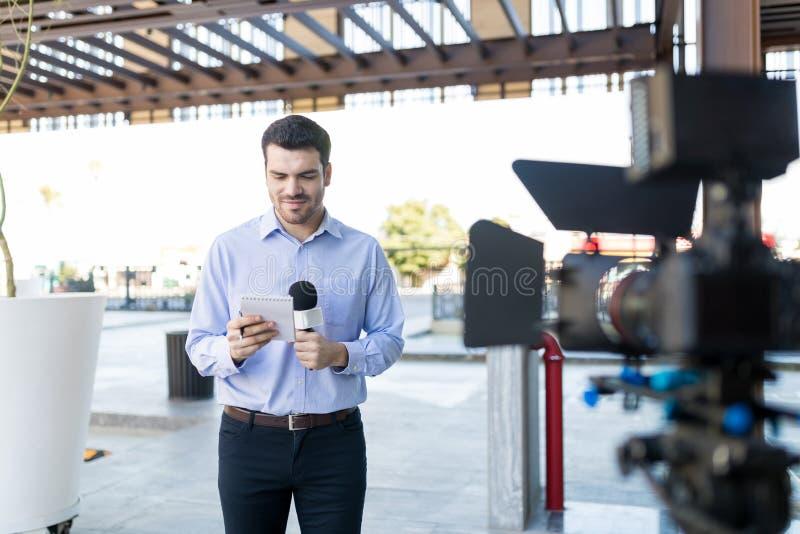 电视记者在广播的读书问题 免版税库存图片
