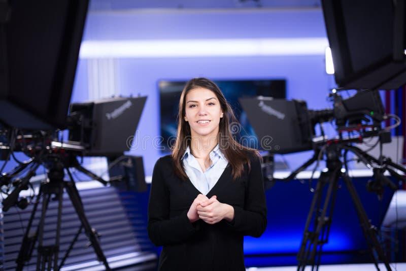 电视赠送者录音在新闻演播室 提出业务报告的女性新闻工作者船锚,记录在电视演播室 免版税图库摄影