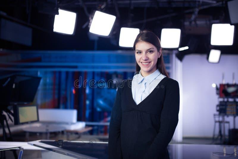 电视赠送者录音在新闻演播室 提出业务报告的女性新闻工作者船锚,记录在电视演播室 库存图片