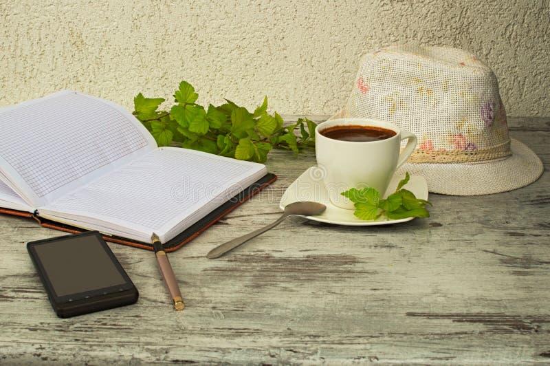 电话、一杯咖啡和帽子 免版税库存照片