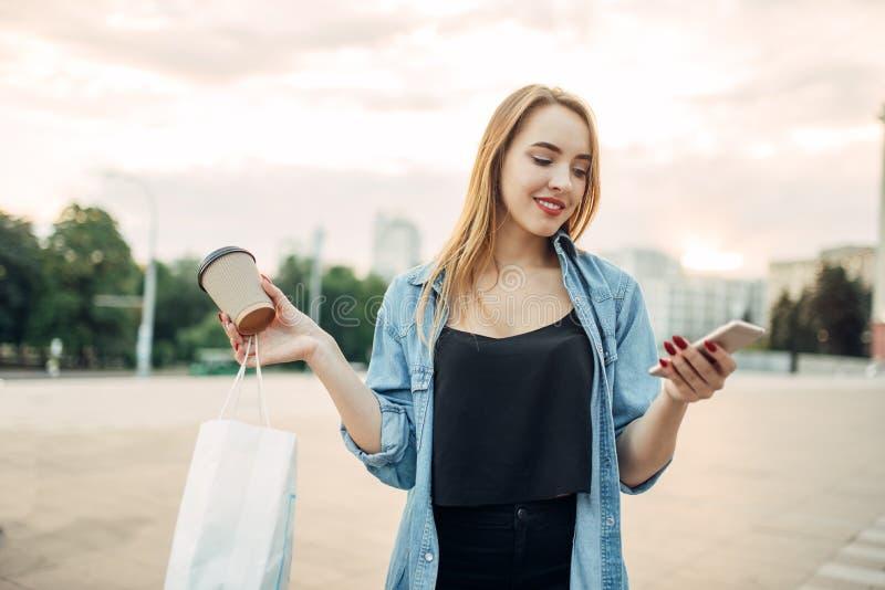 电话上瘾者妇女在手中拿着小配件和咖啡 免版税库存图片