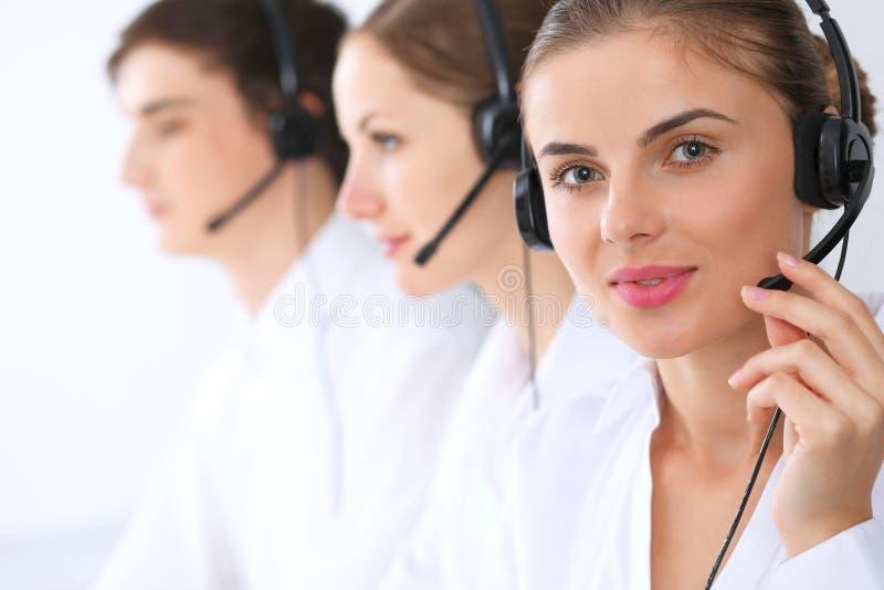 电话中心操作员在工作 在美丽的女商人的焦点耳机的 免版税库存图片