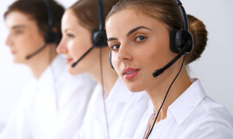 电话中心操作员在工作 在美丽的女商人的焦点耳机的 库存图片