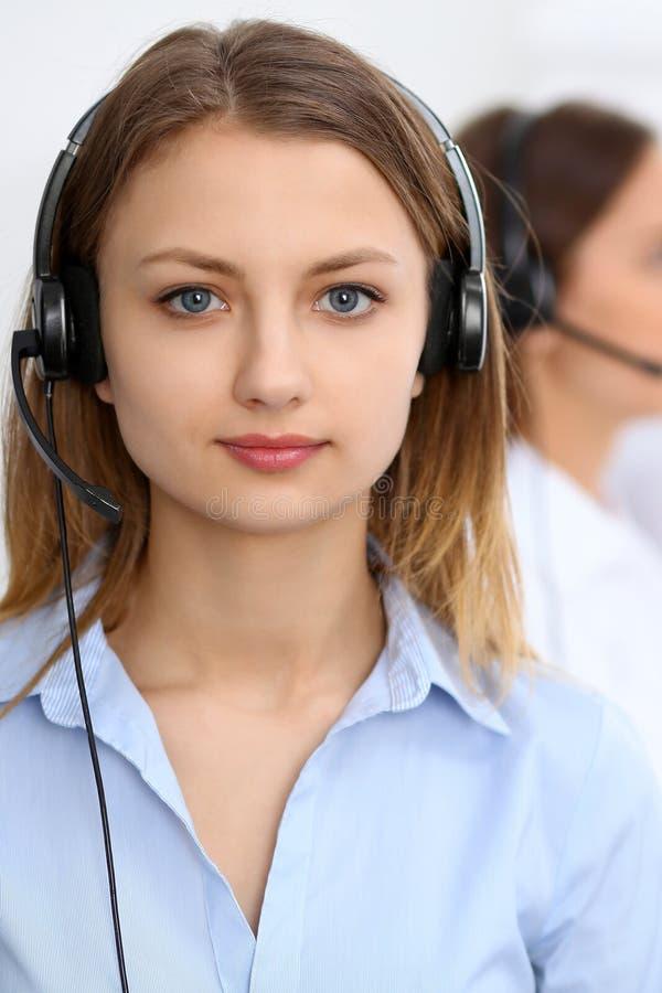 电话中心操作员 聚焦在耳机的年轻美丽的女商人 库存图片