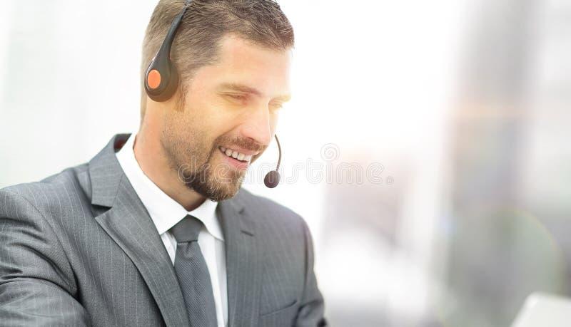电话中心的年轻代理与耳机的 库存照片
