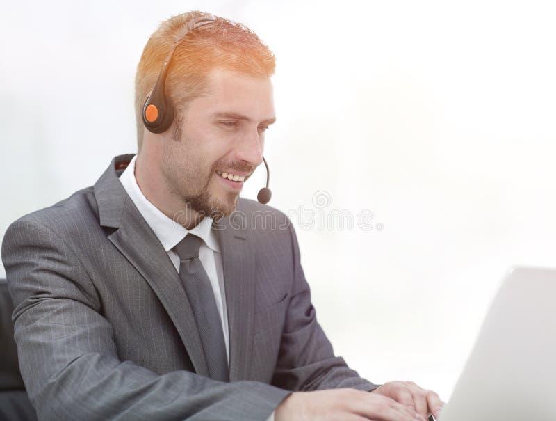电话中心的年轻代理与耳机的 库存图片