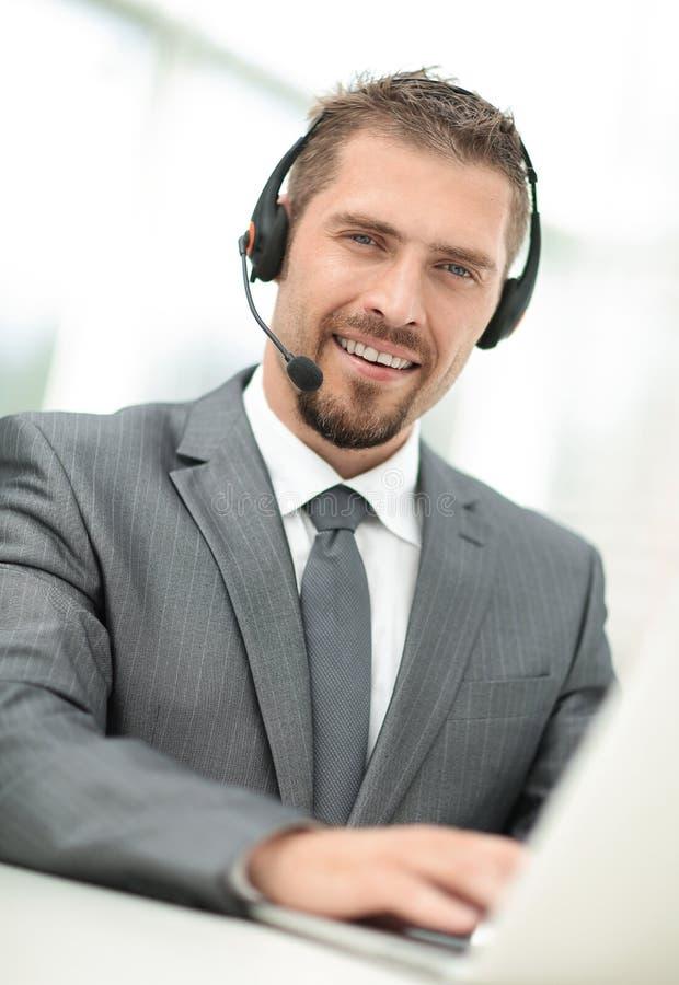 电话中心的年轻代理与耳机的 免版税图库摄影