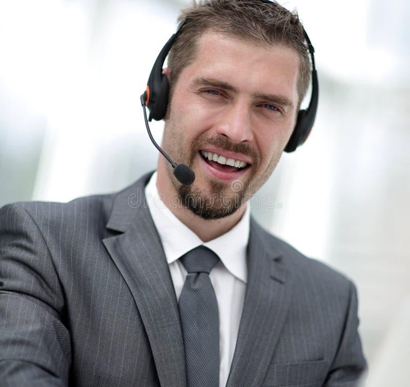 电话中心的年轻代理与耳机的 免版税库存照片