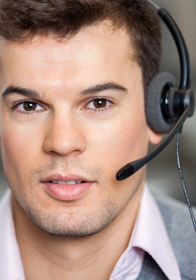 电话中心雇员佩带的耳机在办公室 免版税库存照片