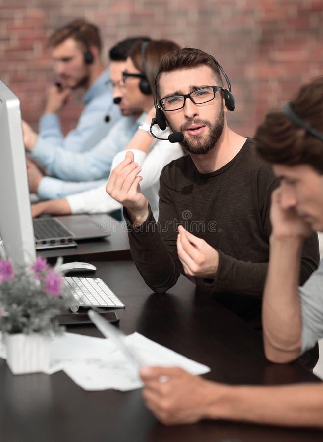 电话中心雇员解释坐在桌上的某事 免版税库存图片