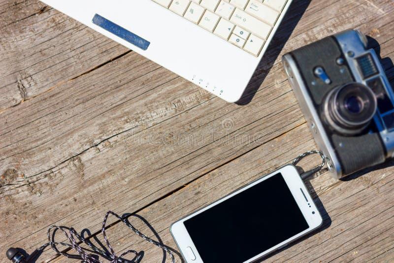 电话和膝上型计算机耳机在木背景说谎 库存图片