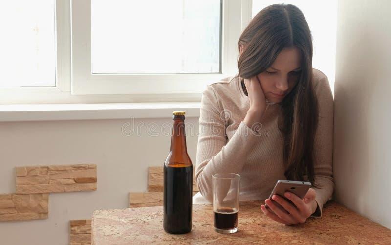 电话和饮料啤酒的年轻美丽的女孩浏览互联网 免版税库存照片